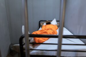 inmate laying in bed